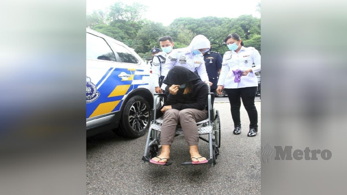 ANGGOTA polis Trafik membawa pemandu Perodua Myvi wanita dengan menaiki kerusi roda yang didakwa di Mahkamah Majistret Johor. FOTO ZAIN AHMED