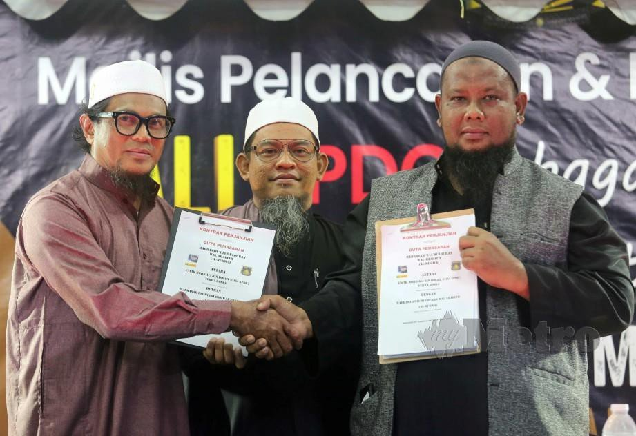 PENGETUA Madrasah Ulumulquran Wal Ahadith (Al-Muqwa), Amran Johari bersama Ali (kiri) ketika Majlis Pelancaran serta Kontrak Penjanjian sebagai Duta Pemasaran di Madrasah Ulumuquran Wal Ahadith (Muqwa Al-Muqwa), Jalan Rantau Panjang, Klang. FOTO MUHD ASYRAF SAWAL