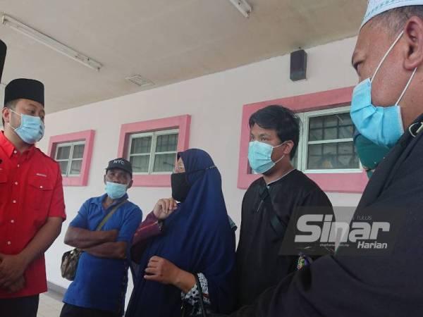 Md Tarmidi(kanan) dan isteri ketika menerima kehadiran Presiden Majlis Gabungan Belia Melaka (MGBM), Mohd Ridhwan Mohd Ali di pekarangan Hospital Melaka di sini, pada Ahad.